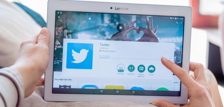 Kadın Lenovo tablete Twitter uygulamasını yüklüyor. Twitter, kullanıcıların mesaj gönderdiği ve bunlarla etkileşim kurduğu bir çevrimiçi haber ve sosyal ağ hizmetidir